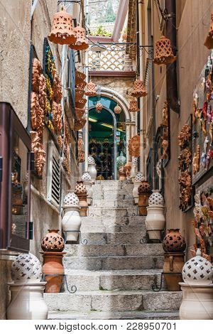Clay or earthenware containers and decorations on a narrow steep stone staircase in Taormina, Sicily leading to an arched window at the top