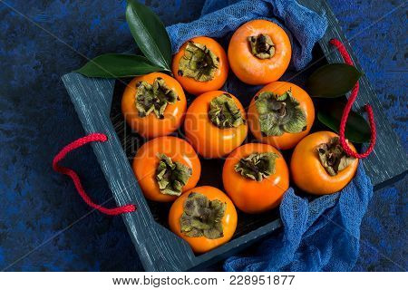 Ripe Persimmon In Box With Blue Gauze Napkin On Blue Textured Background. Persimmon Is Source Of Vit