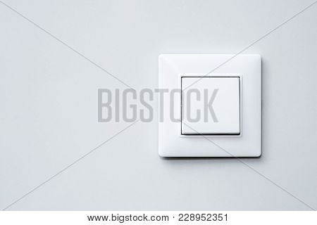 A Light Switch, A Plastic Mechanical Switch Of White Color Installed On A Light Gray Wall.