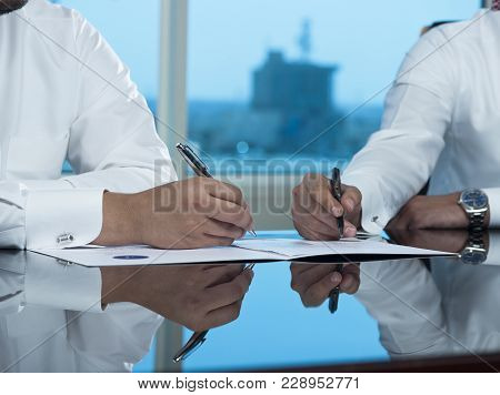 Two Saudi Businessmen Hands Signing A Ducument
