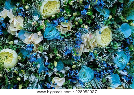Colorful Floral Background Of Blue Roses, Greenish-white Ranunculus, Other Flowers, Leaves And Roots