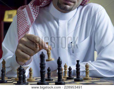 An Arab Man Playing Chess At His Desk