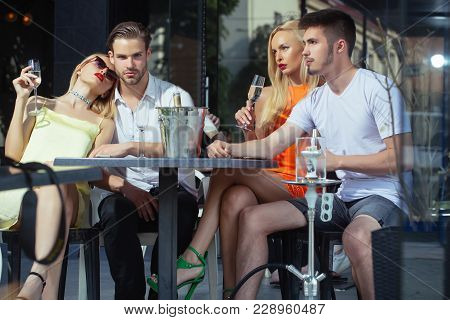 Twins Women And Men Relax In Shisha Cafe Outdoor. Celebration, Party Concept. Friends Vapor Hookah A