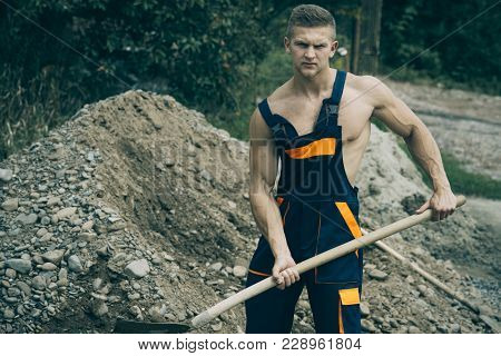 Sexy Man With Nude Torso And Strict Face Works With Construction Equipment Or Shovel With Pile Of Gr
