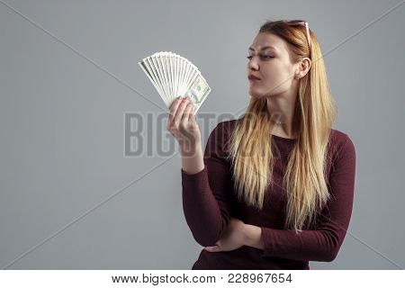 The Image Of A Rich Successful Girl, With Dollars In Her Hands, Is Isolated