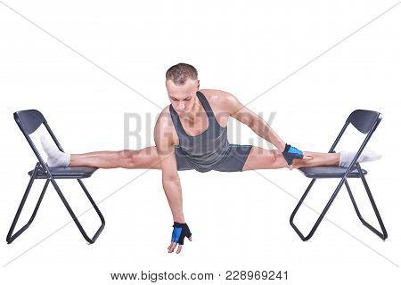 A Handsome Man Performs A Transverse Twine, In Sportswear On Chairs Isolated On A White Background F