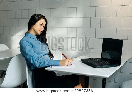 Pensive Woman Sitting At Desk In Office And Writing Something
