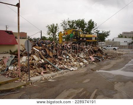 Rubble And Debris From Storm Damage Caused By Hurricane Katrina With A Backhoe On Top Of The Rubble.