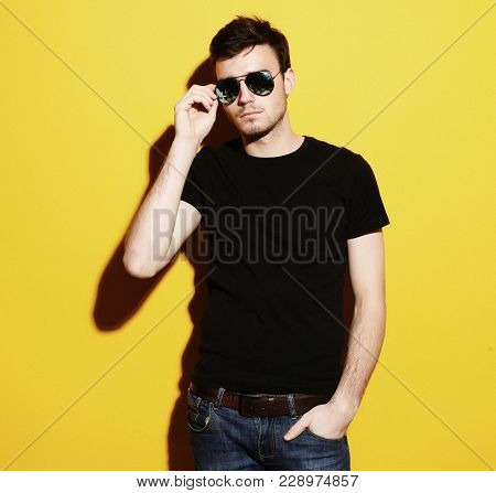 closeup portrait of a young casual man wearing sunglasses  on ye