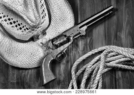 Old Cowboy Pistol ,straw Hat And Rope In Black And White.