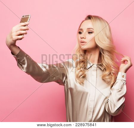 Portrait of beautifu  smiling blond woman in casual clothes with perfect  makeup with smartphone, makes selfie over pink background