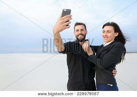 Couple Test Camera In New Smartphone, Boyfriend And Girlfriend Taking Selfies. Fellow In Black Shirt