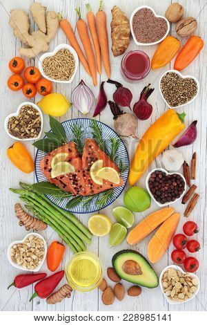 Health food for heart fitness concept with super foods of salmon fish, fruit, vegetables, seeds, nuts, spice and herbs used in herbal medicine and providing omega 3, anthocyanins and antioxidants.