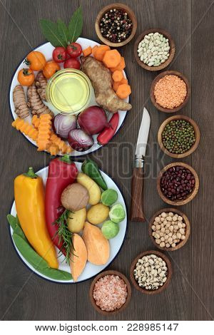 Healthy eating food concept with herbs, spice, vegetables, fruit, olive oil and pulses on rustic oak background. Super foods high in antioxidants, vitamins, minerals and anthocyanins.