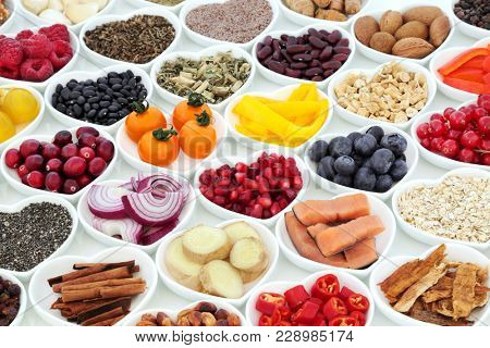 Super food nutrition for a healthy heart with fruit, vegetables, fish, cereals, seeds, nuts. spice and herbal medicine. Foods very high in antioxidants, omega 3,  fibre, anthocyanins & vitamins.