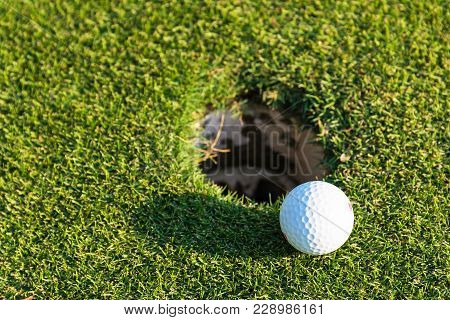 Golf Ball On Green Over A Blurred Hole. Shallow Depth Of Field. Focus On The Ball. Sport Concept ,li