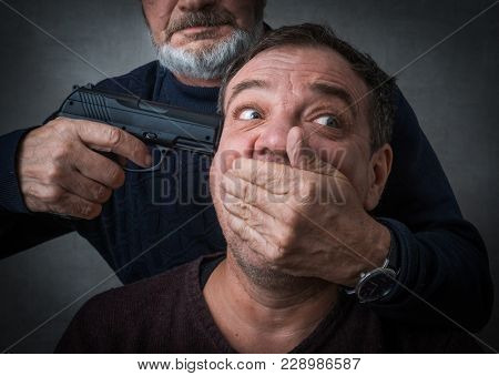 Killer with a gun and his victim a hostage