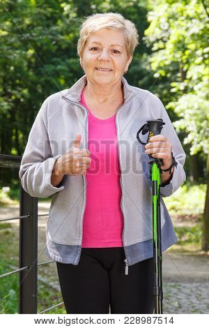 Elderly Senior Woman In Sporty Clothes Holding Nordic Walking Sticks And Showing Thumbs Up, Healthy