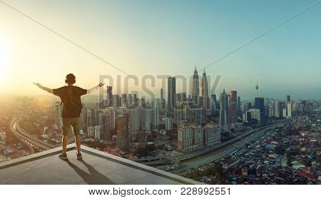 Young man stand at rooftop looking great cityscape sunrise view and praying .