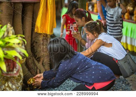 KOH CHANG, THAILAND - MAR 1, 2018: Locals during celebration of Makha Bucha Day. One of the three most important holidays of Buddhism, which dictates its social norms to locals and foreign tourists.