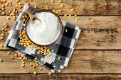 Bowl with corn starch and kernels on wooden table poster