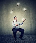 Young chubby man sitting on chair and juggling with light bulbs being genius. poster