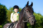 Little girl riding in summer with her horse poster
