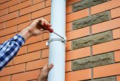 Worker Installing rain gutter downspout pipe. Contractor hands repair rain gutter downspout pipe with screwdriver. Guttering, Rain Chain, Plastic Guttering & Drainage. poster