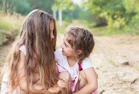 Beautiful Young Girls With Long Hair, Smiling And Talking At Summer Day. Having Fun Otdoors