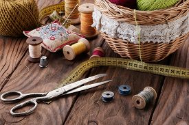 Bundles Of Thread In A Basket, Scissors And Thread In Drums On A Wooden Table Close-up
