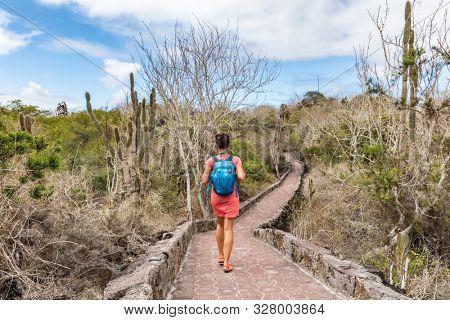 Galapagos Islands tourist exploring wildlife and ecotourism adventure walking on path to Tortuga Bay beach in Santa Cruz island. Woman on Galapagos islands travel vacation. poster