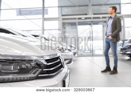 Selective Focus Of Headlights Of Big White Car In Auto Salon. Young Male Customer Looking At New Car