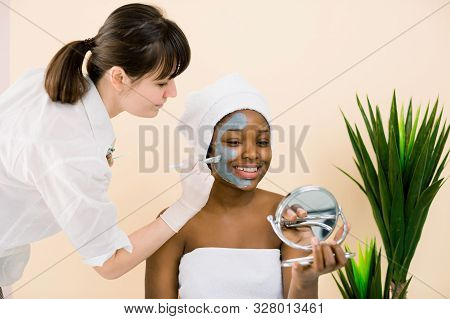 Pretty Ypung African Woman In White Towel During Facial Routine, Applying Mask, Watching In The Mirr