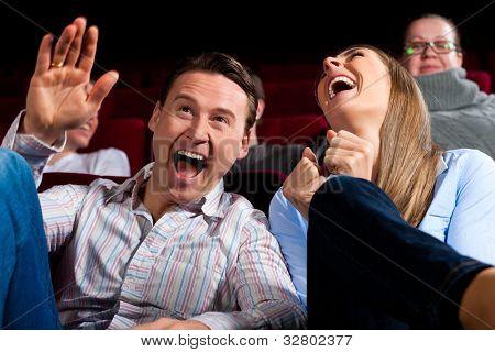 Casal e outras pessoas, provavelmente de amigos, no cinema, assistindo a um filme, parece ser um filme engraçado