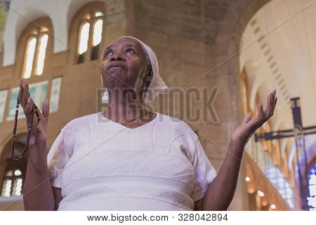 Aparecida, São Paulo, Brazil - January 13, 2016: Faithful Afro -brazilian Woman Prays At Cathedral O