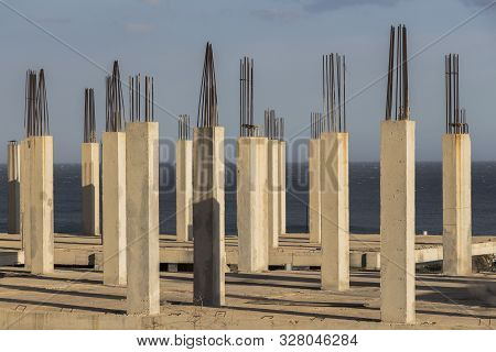 concrete pillars with sea in the background, concrete formwork poster