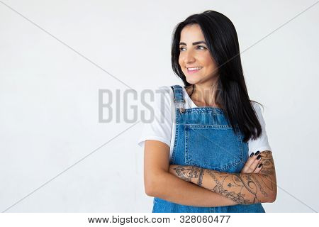 Joyful Attractive Young Brunette With Crossed Arms. Cheerful Brunette Lady Looking Aside On Light Ba