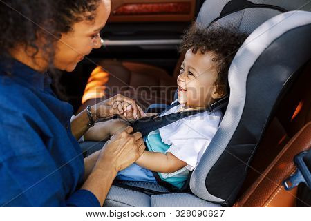 Side View Of A Mother Helping Toddler Get Buckled Into His Car Seat