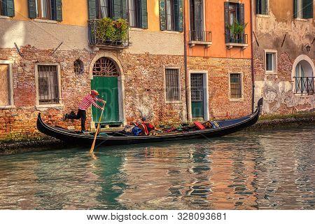 Venice, Italy - October 11, 2019: Tourists Travel On Gondola At Canal In Venice, Italy . Gondola Tri