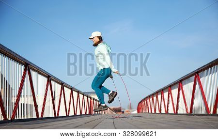 Woman Jumping Rope On A Wooden Bridge, Cardio Exercise Outdoors, Taking Care Of Her Body, Staying He