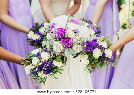 The Bride And Bridesmaids Are Holding Bouquets Of Flowers.
