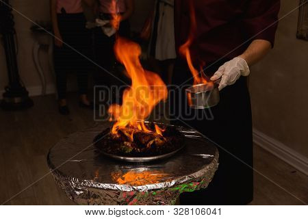 Chef, Pouring Alcohol Into A Frying Table With Fire. Appetizing Grilled Meat On Fire Close-up. Beaut