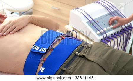 Close-up. Electrical Stimulation Procedure For Abdominal Muscles. A Man Passively Stimulates The Abd