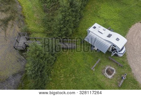 Modern Rv Class C Camper Van Parked On Beautiful Camping Spot With Access To Small Pond. Aerial Phot