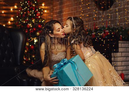 Family Celebrates Christmas. Happy Mother With Daughter In Magic Night. Sharing Christmas Presents O
