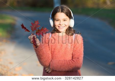 May This Autumn Be As Melodious As Happy Song. Happy Small Girl Listen To Music On Autumn Landscape.