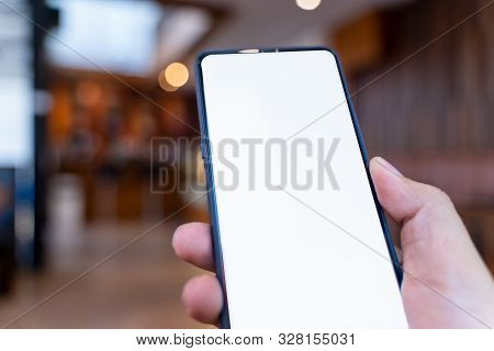 Man Holding Smartphone With White Blank Screen At Coffee Shop .blank Screen Mobile Phone For Graphic