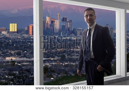 Businessman Wearing A Suit Looking At The Buildings Of Downtown Los Angeles From An Office Window.