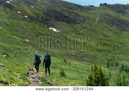 Hiking With Backpacks On A Beautiful Rocky Trail On A Warm Sunny Day. The Concept Of Family Travel A