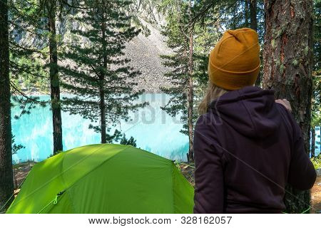 A Girl Wearing A Knitted Hat And Sports Tourist Clothing Stands By A Green Tent And Looks At A Amazi